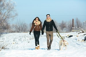 Young couple in love walking with dog