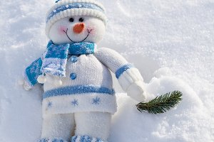Toy snowman on a snowy background.