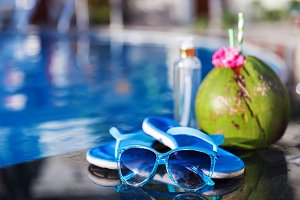 Coconut drink juice oil, slippers and sunglasses