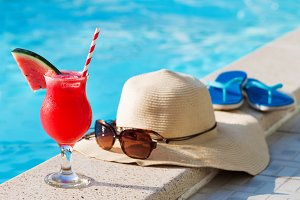 glass of water-melon smoothie drink sunglasses hat