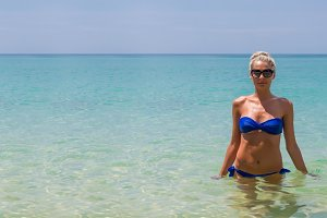slim blonde woman swimming on tropic beach