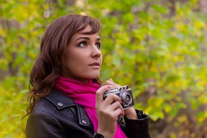 brunette woman with a photo camera in autumn park