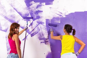 women paints white wall with purple paint roller