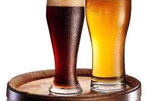 glasses of beer over woden barrel.