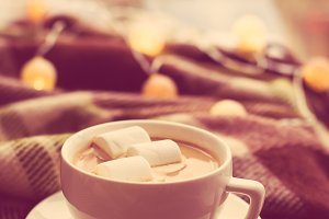 cup of coffee with marshmallows, warm blanket and Christmas ligh