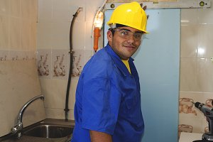 Construction worker with yellow helmet building a kitchen