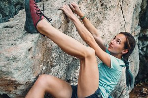 Woman bouldering the rocky stone