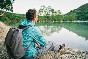 Traveler sitting on shore of lake