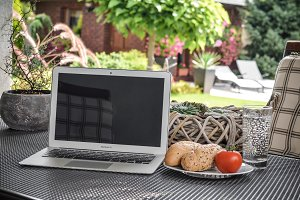 Laptop on table with breakfast