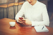 Smiling beautiful woman using smart phone in cafe and restaurant