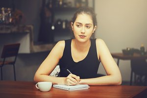 Young Caucasian woman thinking and writing something on a notebook in cafe