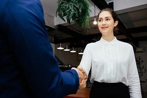 Caucasian business woman shaking hands with business man in the modern interior office - Business and partnership concept