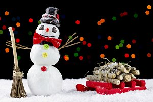 Snowman and sled with bokeh lights background