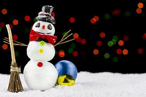 Snowman on bokeh lights background