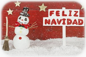 A snowman with a signpost with the words Merry Christmas on spanish