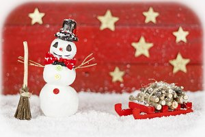 Snowman with sleigh on red background