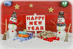 Two snowmen and a sign with the words Happy New Year