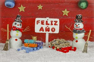 Two snowmen and a sign with the words Happy New Year on spanish