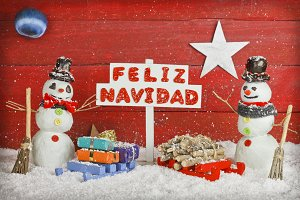 Two snowmen with a sign with the words Merry Christmas written on spanish