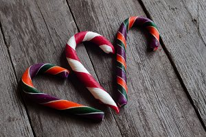 Three candy canes on a wooden background.