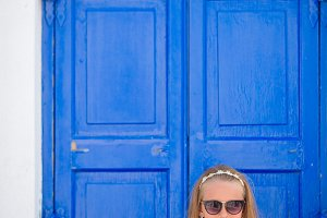 Little girl in white dress in old streets an Mykonos.