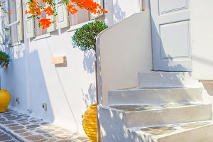 The narrow streets with blue balconies, stairs, white houses and flowers in beautiful village in Greece. Beautiful architecture building exterior with cycladic style in Mykonos
