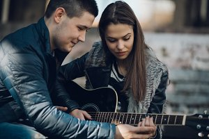 Teenage couple playing guitar