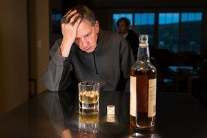 Depressed senior man taking to drink