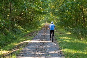 Senior lady cyclist on forest trail