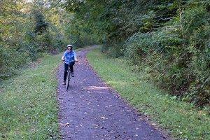 Senior lady cyclist on forest trail