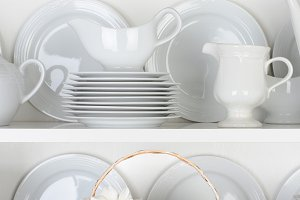 White Plates in Cupboard With Roses