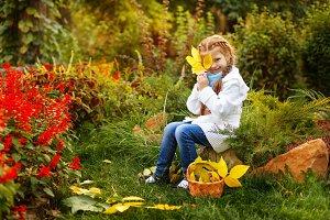 Girl hides face behind leaf