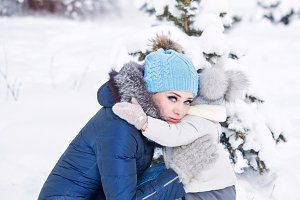Mother and daughter hug in winter