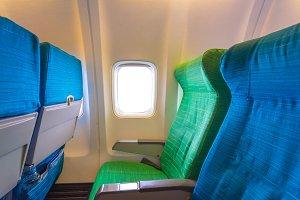 Airplane seat near windows in cabin