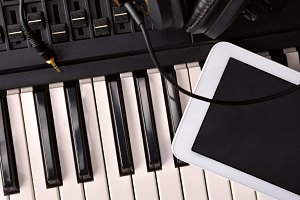 Piano, headphones and tablet studio