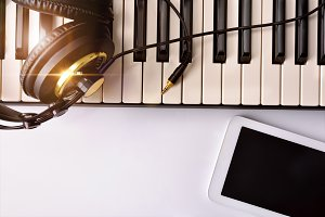 piano with headphones and tablet