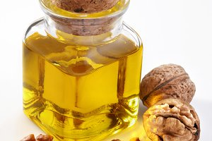 Walnut oil with nuts on a white