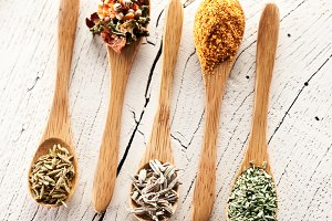 Variety of spices in the spoons on an white old wooden table.