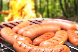 Sausages on a grill. In the background a bonfire in the forest.