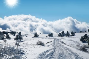 Winter landscape. The road going to horizon above the clouds.
