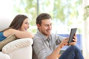 Cheerful couple using a tablet