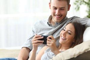 Happy couple enjoying media content
