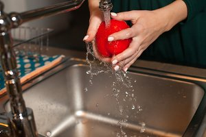 Woman is washing a pepper