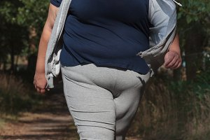 Overweight woman walking outdoors