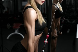 Woman Exercising Back On Machine In The Gym