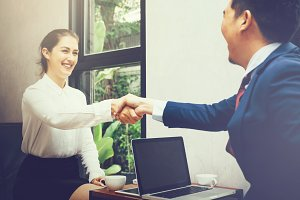 Business woman shaking hands with business man in the modern interior office - Business and partnership concept