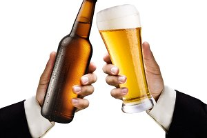 Two men's hands with a glass and a bottle of beer on white background.