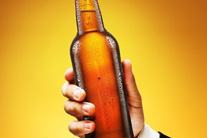 Bottle of beer in a man's hand on a yellow background.