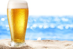 cold beer glass in the sand.