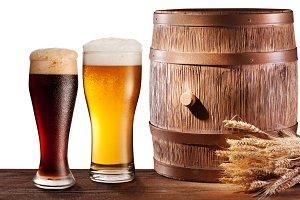 glasses of beer near woden barrel.